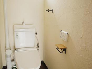 長岡京市の中古マンションリノベーション。リフォーム後のトイレ。トイレの壁も漆喰、横の配管も白く塗りました。