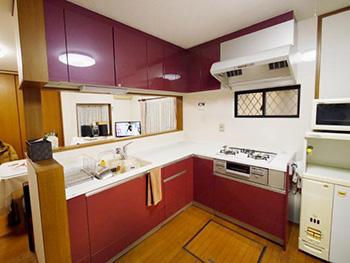 長岡京市のキッチンリフォーム。リフォーム後のキッチンです。落ち着いた赤色のキッチンです。吊戸棚も同じ赤色に。
