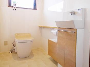 長岡京市のトイレリフォーム。リフォーム後のトイレです。とても明るいトイレになりました。白い壁と、木目調の便器と手洗い器です。