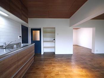 大山崎町の円団団地リノベーション。木目調とステンレスの壁付けキッチン。キッチンの壁は奥様お気に入りの白い横長のタイルを張りました。キッチン入口の青いドアの横には、大きな4段の棚を造りました。