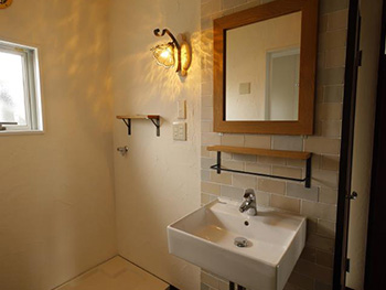 長岡京市の中古マンションリノベーション。洗面室にはオレンジ色の電球色のガラスの電気を。鏡の下に四角い洗面台を付けました。