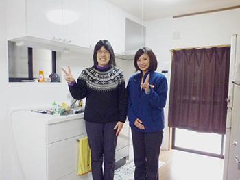 大山崎町の水廻りリフォーム。システムキッチンも新しくなりました。白いシステムキッチンになり、お台所が明るくなりました。素敵な笑顔のお客様と営業担当の女性の記念撮影です。パナソニック リビングステーションSクラスI型2550 アルベロホワイト