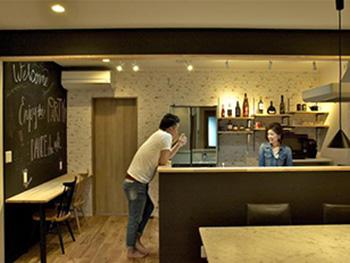 大山崎町のリビングリノベーション。リフォーム後のキッチンカウンターで、ご夫婦で会話をされています。後ろのあ棚にはお酒が並び、スポットライトが当たってとても素敵。
