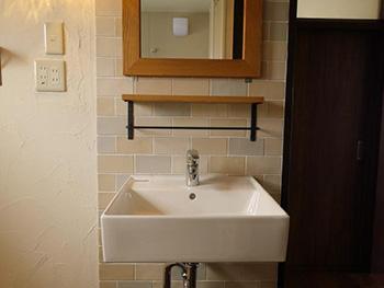 長岡京市の中古マンションリノベーション。鏡と洗面台の後ろの壁は、タイル張りです。