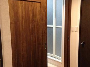 お風呂浴室リフォーム。洗面室の入口ドアは引き戸になりました。濃い茶色の建具です。