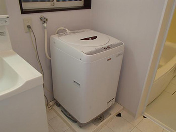 大山崎町の浴室・洗面室リフォーム。リフォーム後の洗面室に洗濯機が置かれています。全自動洗濯機がぴったり収まる洗濯パンを取り付けました。洗濯機のホースが抜けても、水が緊急ストップする蛇口も取り付けました。