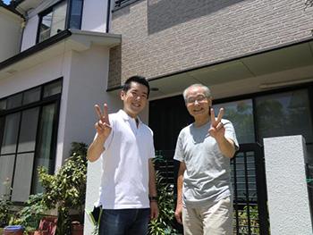 長岡京市の外壁塗装とバルコニー増築リフォーム。リフォーム後のお家前でお施主様と記念写真。お客様はニコニコ笑顔でピースサインをして下さっています。