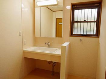 長岡京市の店舗をリビングにリフォーム。リフォーム後の洗面室。鏡が大きくなったからか広く見える洗面室です。