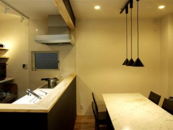 大山崎町のリビングリノベーション。キッチン前に置かれたダイニングテーブルの上には、ペンダント照明をレールに3つ取付けました。