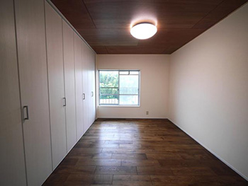 大山崎町の円団団地リノベーション。焦げ茶色のフローリングの洋室です。壁とクローゼットはホワイトです。クローゼットの中に、用途サイズに合った棚を取り付けました。