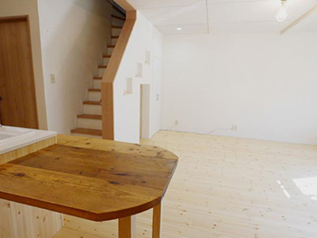 ライオンホームのリビングリノベーション。キッチンの前に2階へ上がる階段が見えます。