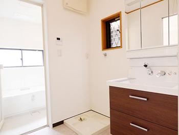 向日市で中古住宅を購入してリノベーション。リフォーム後の脱衣所兼洗面室です。こげ茶色の引出の洗面台。