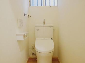 真っ白の壁にアイアンのタオル掛けが付いたリフォーム後のトイレです。