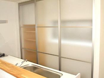 長岡京市の中古住宅リフォーム。キッチン後ろには3枚の引き戸を付けました。シルバーの枠にすりガラスのような形状で、収納棚が丸見えでは無い程度に隠せます。引き戸を閉じたままでも窓からの光が入ります。パナソニック アルポルタ3枚引き戸。