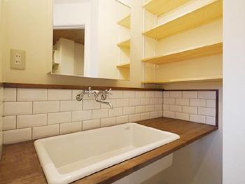 大山崎町の円団団地リノベーション。リフォーム後の洗面台です。濃いブラウンの木にTOTOの実験用洗面ボウルが取り付けてあります。壁は白い横長のタイルです。
