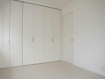 長岡京市の中古住宅リフォーム。リフォーム後の2階の洋室。クローゼット、壁、ドア、フローリング全て白が基調のお部屋です。