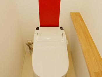 長岡京市の中古住宅リフォーム。リフォーム後のトイレです。便器の後ろ側の壁に赤のクロスを細長く貼りました。赤が効いています。パナソニック アラウーノS。