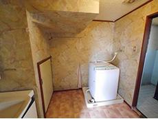 長岡京市のお風呂浴室リフォーム。リフォーム前の洗面室は、壁が大理石調でした。洗濯機が置かれています。