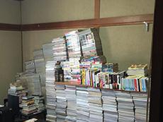 ライオンホームでリノベーション。リフォーム前の和室です。文庫や雑誌などのたくさんの本が部屋いっぱいに積み上げられている状態です。