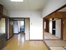 大山崎町の円団団地リノベーション。リフォーム前の玄関を入ると、キッチンと和室が続いています。