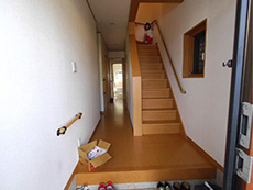 向日市で中古住宅を購入してリノベーション。リフォーム前の玄関を入ったところです。2階への階段も玄関の廊下と同じキャラメルブラウンの木材です。