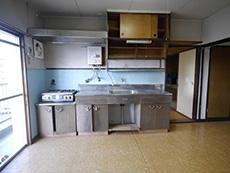 大山崎町の円団団地リノベーション。48年前のキッチンです。古い木の開き戸収納に壁は水色のタイル貼りです。