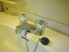 ライオンホームの洗面台リフォーム。古い洗面台に付いている水栓は、水とお湯、ひねる蛇口。