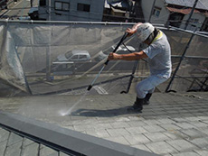 長岡京市の屋根外壁塗装リフォーム。塗装前の必要な作業、屋根の長年の汚れやコケを高圧洗浄機で洗い流しています。