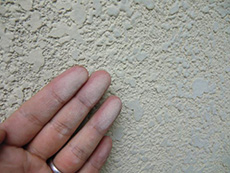 向日市の外壁塗装リフォーム。外壁を触った手が白くなっています。これはチョーキング現象というものです。塗膜が痩せた状態である証拠です。