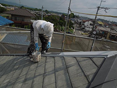 長岡京市の屋根外壁塗装リフォーム。屋根の板金に錆止めを塗っています。