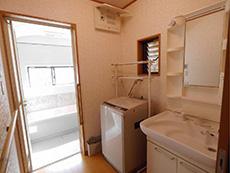 向日市で中古住宅を購入してリノベーション。リフォーム前の脱衣所兼洗面室です。浴室のドアが開いて浴室が見えています。