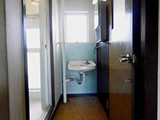 大山崎町の円団団地リノベーション。浴室前の廊下の突き当りに剥き出しの小さな洗面台があります。後ろの壁が水色のタイル張りです。
