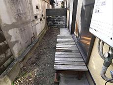 向日市で中古住宅を購入してリノベーション。家から出られる、奥行きの狭い横に細長い裏庭です。縁台の木が朽ちています。