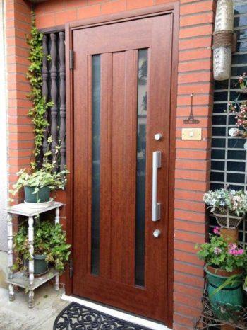 大山崎町の玄関ドアリフォーム。壁を壊さずにドアの交換が出来るように、ドアを特注しました。ポートマホガニーという色で、赤みがかった茶色が素敵です。縦に2列ガラスの明り取りが入っています。