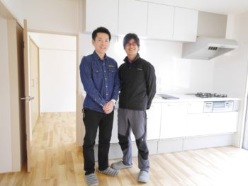 大山崎町の中古円団マンションリノベーション。リフォーム後のキッチンの前で、爽やかな笑顔のO様のご主人とライオンホームの代表・田村が二人で記念撮影をしました。