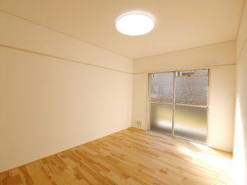 大山崎町の中古円団マンションリノベーション。リフォーム後の洋室です。壁のクロスと床のフローリングを張り替えました。とても明るい印象です。