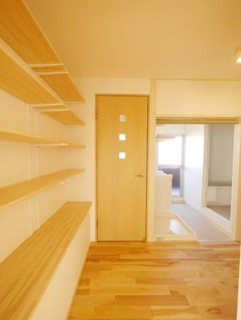 大山崎町の中古円団マンションリノベーション。トイレのドア前です。ドアには小さな明かり取りの窓が縦に3つ並んでいます。ドアの手前の壁には幅の広い飾り棚を何段も造りました。