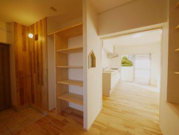 大山崎町の中古円団マンションリノベーション。リフォーム後の玄関からキッチンへ入る場所です。まるで木の香りが漂うような玄関です。