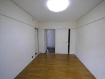 大山崎町の中古円団マンションリノベーション。白いクロスとフローリングの洋室。幅の狭い片側だけの押入れ収納が一つあります。