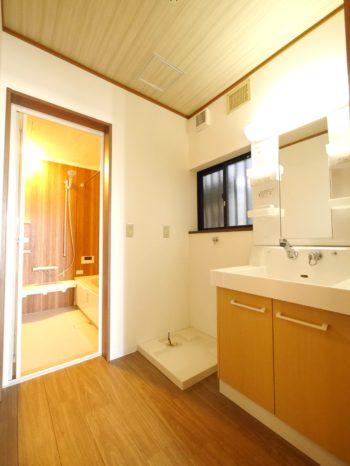 向日市の中古住宅リノベーション。リフォーム後の1階の洗面室。白い洗面台は、扉だけが明るいブラウンです。