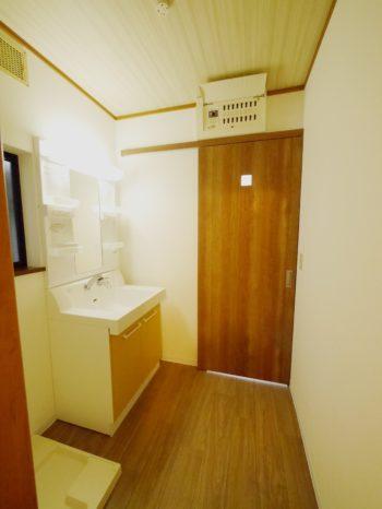 向日市の中古住宅リノベーション。洗面室の入口扉です。洗面室の床、洗面台の扉、浴室のアクセント壁のブラウンの木目調と色味を合わせた引き戸。