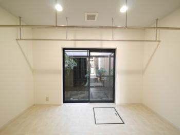 向日市の中古住宅リノベーション。リフォーム後の、1階一番奥にある、ランドリールーム。室内にお洗濯ものが干せるように、天井に竿のようなパイプを付けています。