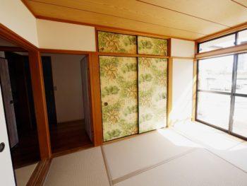 向日市の中古住宅リノベーション。リフォーム後の1階和室。淡い黄色の壁の部屋にある襖です。大柄の植物模様のボタニカル柄のクロスは奥様のDIY。襖に貼っています。