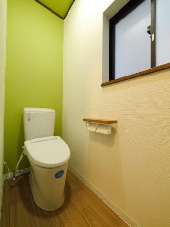 向日市の中古住宅リノベーション。リフォーム後の2階のトイレ。アクセントに黄緑のクロスが壁と天井に貼られています。白とグリーンで明るいトイレです。