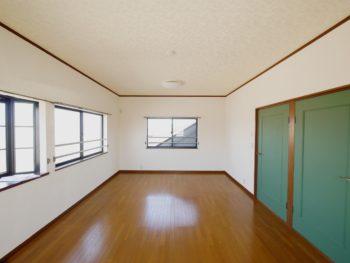 向日市の中古住宅リノベーション。リフォーム後の3階の子ども部屋。12畳の洋室です。光沢のあるブラウンのフローリングに白い壁のお部屋。2ヶ所あるグリーンの扉は、一つは出入口、もう一つは収納庫になっています。