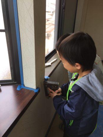 向日市の3階建て中古住宅リフォーム。タッカーという道具を男の子が壁に押し付けています。今からリフォームでキレイにするので、壁に落書きをしてもクロスを破いても何の問題もありません。