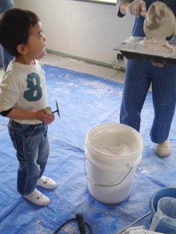 今から壁に漆喰を塗ります。板に、出来上がった漆喰を乗せて、それをコテですくって壁に塗っていきます。横で見ている小さい男の子がワクワクしているのがわかります。