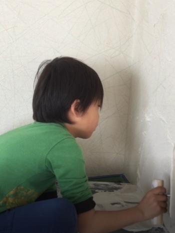 向日市の3階建て中古住宅リフォーム。壁に漆喰を塗っている男の子です。壁の下の方は塗りにくいのですが、丁寧に塗っていてとても上手です。