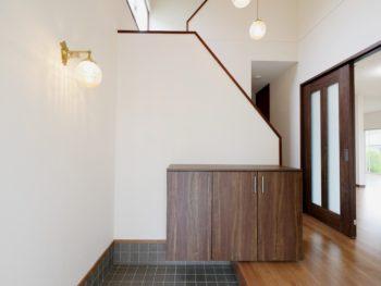 長岡京市の中古住宅リノベーション。リフォーム後の玄関。吹き抜けまでクロスを張り替えて、白い壁がまるで新築のようです。