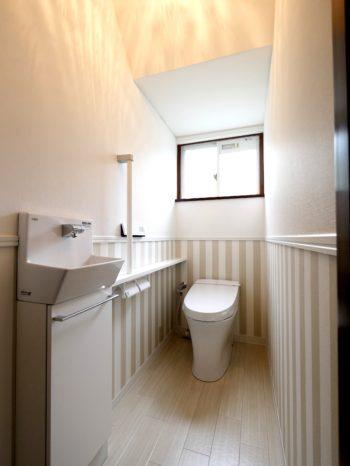 長岡京市の中古住宅丸ごとリフォーム。リフォーム後の1階のトイレ。壁に見切りを入れて、上下でクロスを替えています。下は白とベージュの太いストライプ。上は白に。